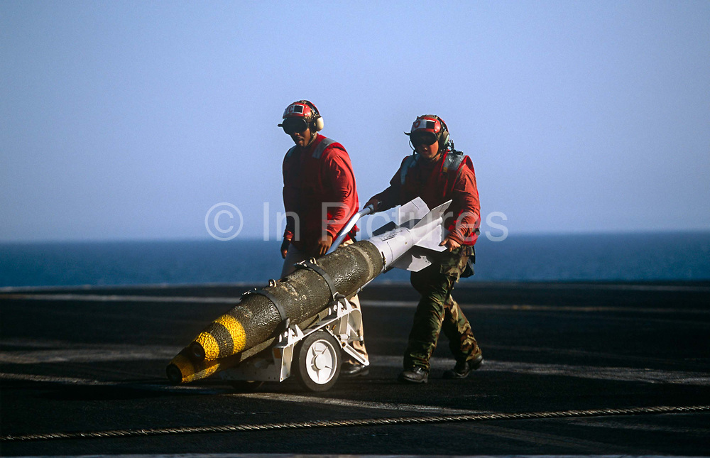 Red shirted ordnance men prepare to fit smart bombs to an F/A-18 fighter jet on deck of USS Harry S Truman. Launched on 7 September 1996 and costing US$4.5 billion, the Truman (CVN-75) is the eighth Nimitz-class supercarrier of the United States Navy, named after the 33rd President of the United States, Harry S. Truman. The Truman is the largest of the US Navy's fleet of new generation carriers, a 97,000 ton floating city with a crew of 5,137, 650 are women.