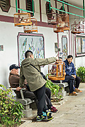 Chinese men socialize with their songbirds at the Yuen Po Street Bird Garden in Mong Kok, Kowloon, Hong Kong.