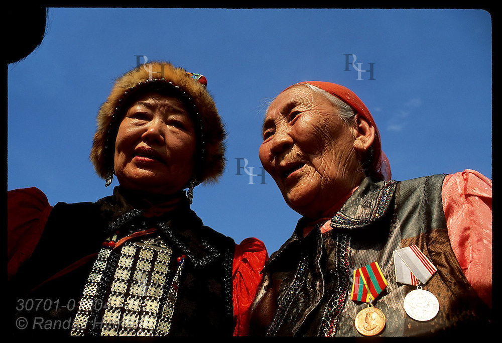 Old Sakha woman w/ medals talks to younger woman in fur cap at midsummer Ysyakh fest; Yakutsk. Russia