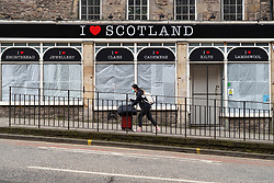 Edinburgh, Scotland, UK. 18 April 2020. Views of empty streets and members of the public outside on another Saturday during the coronavirus lockdown in Edinburgh. Closed and boarded tourist souvenir shop. Iain Masterton/Alamy Live News