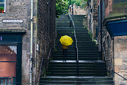 Edinburgh, Scotland, UK. 29 June, 2020. Heavy rain, cold temperatures and wind in Edinburgh today.  A lone member of the public with yellow umbrella  climbs the Vennel steps, now renamed the Miss Jean Brodie steps, at Grassmarket in the Old Town.  Iain Masterton/Alamy Live News