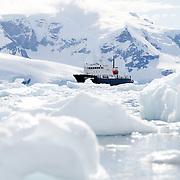 A ship (Polar Pioneer) amongst the brash ice and icebergs of Neko Harbour, Antarctica.