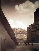 Cañon del Muerte, Navajo, c1906.   Four horsemen dwarfed  by rock formations.