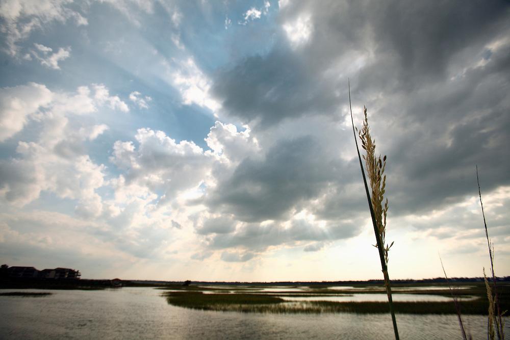 Sunbeams shine through a cloudy sky over a marsh at Wrightsville Beach.