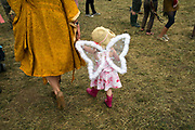 A mother leads her child through a field dressed as an angel at the Standon Calling Festival in Hertfordshire, UK<br /> Standon Calling is a small independent festival set among the hills in Herfordshire that showcases World Music, Indie Music and dance Music. It is one of the new, small and quirky boutique festivals which have become popular in the UK.