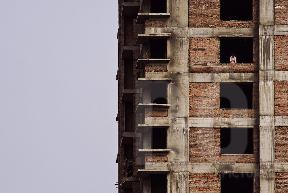 A silhouette shows out of an unfinished window frame in a building in construction. Hanoi, Vietnam, Asia