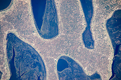 An astronaut aboard the International Space Station took this photograph of the strange rounded shapes along the coastline of Zambia's Chilubi Island. The light-toned sand island stands out from the dark waters of Lake Bangweulu.<br /> In the photo we see a few patches of open water between the fingers of the island. The waters are crowded by areas of aquatic vegetation and wetland (reeds, papyrus, and floating grass) in green. Lake Bangweulu, which is only 4 meters (13 feet) deep on average, is rich enough to supply fish for the copper-mining towns to the west.<br /> Chilubi Island has 100 kilometers (60 miles) of coastline, providing prime access to the richest fishing waters in northern Zambia. Those coastlines are smoothed by easterly winds that erode ancient sand dunes. The narrow strips of lighter toned land along the shorelines are areas that have been mostly denuded of vegetation by residents of the densely populated fishing villages.<br /> The explorer and missionary David Livingstone was the first European to visit the lake (1868).<br /> Astronaut photograph ISS044-E-00661 was acquired on June 14, 2015, with a Nikon D4 digital camera using an 1150 millimeter lens, and is provided by the ISS Crew Earth Observations Facility and the Earth Science and Remote Sensing Unit, Johnson Space Center. The image was taken by a member of the Expedition 44 crew. The image has been cropped and enhanced to improve contrast, and lens artifacts have been removed. The International Space Station Program supports the laboratory as part of the ISS National Lab to help astronauts take pictures of Earth that will be of the greatest value to scientists and the public, and to make those images freely available on the Internet. Additional images taken by astronauts and cosmonauts can be viewed at the NASA/JSC Gateway to Astronaut Photography of Earth. Caption by M. Justin Wilkinson, Texas State University, Jacobs Contract at NASA-JSC.<br />  *** Please Use Credit from Credit Field 