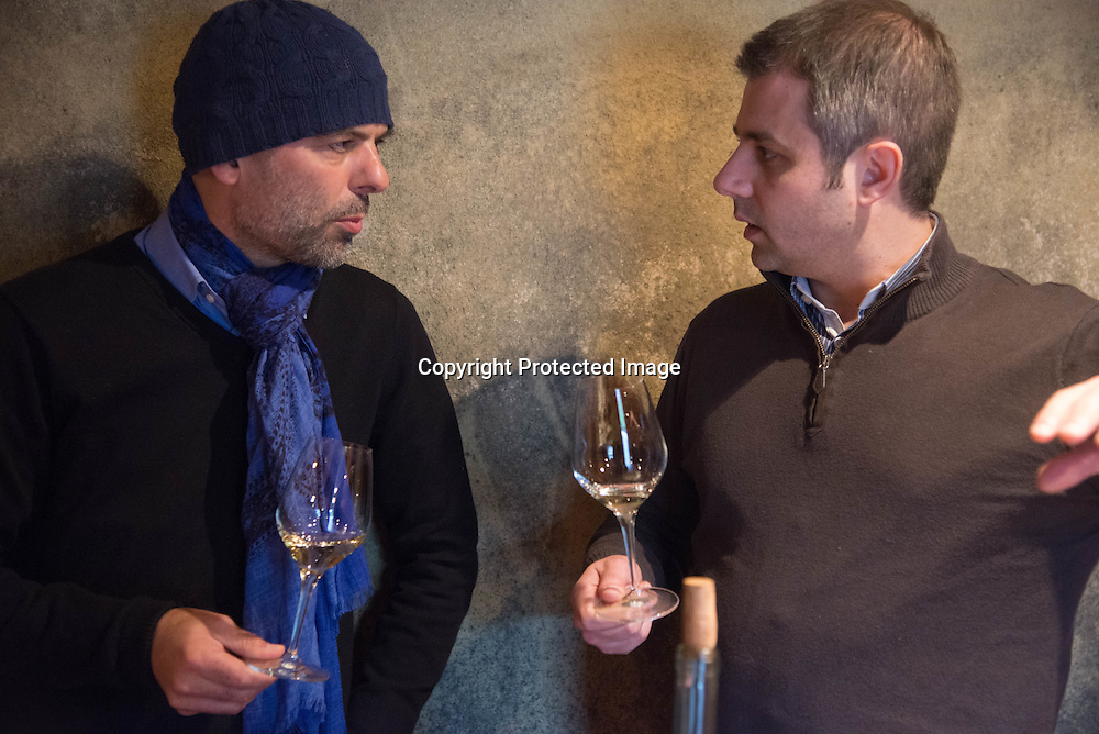 France. Alsace, Andre Ostertag , famous wine maker and Hugues Pouget testing Vendanges tardives  wine and a kiwi cake in a cellar