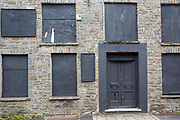 Black boards cover up the windows and doors of the derelict Pentre Inn, Pentre village, Rhondda Valley, South Wales, UK.