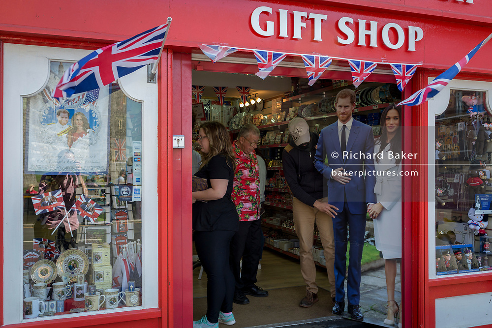 A life-size standee of Prince Harry and Meghan Markle with souvenirs and merchandise on sale in a the doorway of a tourist trinket window as the royal town of Windsor gets ready for the royal wedding between Harry and his American fiance, on 14th May 2018, in London, England. (Photo by Richard Baker / In Pictures via Getty Images)