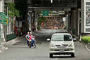 16 MAY 2010 - BANGKOK, THAILAND: A car and motorcycle taxi leaving the area near the Red Shirt camp are the only vehicles on Phloen Chit Road Sunday. The Red Shirts' bamboo wall is at the end of the road. Phloen Chit is normally one of the busiest roads in Bangkok and leads into the city's main shopping district. Thai troops and anti government protesters clashed on Rama IV Road again Sunday afternoon in a series of running battles. Troops fired into the air and unidentified snipers shot at pedestrians on the sidewalks. At one point Sunday the government said it was going to impose a curfew only to rescind the announcement hours later. The situation in Bangkok continues to deteriorate as protests spread beyond the area of the Red Shirts stage at Ratchaprasong Intersection. Many protests now involve people who have not been active in the Red Shirt protests and live in the area of Rama IV. Red Shirt leaders have called for a cease fire, but the government indicated that it is going to go ahead with operations to isolate the Red Shirt camp and clear the streets.      PHOTO BY JACK KURTZ