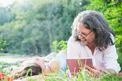 Couple lying side by side using digital tablet by lake, Germany