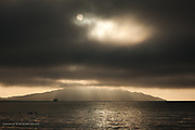 A full sun, semi obscured by a blanket of cloud. Crepuscular rays burst over the trawler in Holyhead Harbour, with the mass of Holyhead Mountain losing it's summit to the low cloud base.