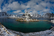 Rorbuer (traditional fisherman's cottages) at Sakrisoy, with winter snow on the mountains beyond, from Olenilsoy, near the village of Reine, Lofoten Islands, Arctic Norway