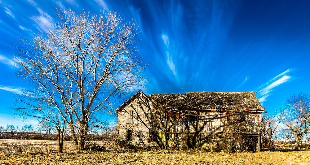 Old barn off Seminole Highway in Fitchburg falling into ruins under brilliant blue sky and wispy clouds on a January day in 2020. Photo taken January 8, 2020.