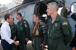 France's President Emmanuel Macron greets helicopter crew before leaving Pointe-a-Pitre airport, Guadeloupe island, en route to French Caribbean islands of St. Martin and St. Barthelemy, Tuesday, Sept. 12, 2017. Macron is heading to the French-Dutch island of St. Martin, where 10 people were killed on the French side and four on the Dutch, to meet with residents. (AP Photo/Christophe Ena, Pool)