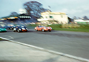 """Blurry photo of British Sports racing driver Bill de Selincourt (1921-2014) driving Lister-Jaguar """" Knobbly"""" car 33, BARC event Goodwood, March 1961 start of the race, John Coundley in brown Jaguar E-type car"""