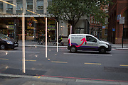 Vertical lighting from Pret a Manger chilled food cabinets and the arrow of a courier delivery van with courier.co.uk, on 17th October 2017, in the City of London, England.