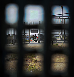 US Border Patrol seen through the fences that divide US and Mexico, seen from the Mexican side at Tijuana.
