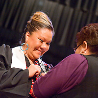 121712       Brian Leddy<br /> Cheryl James receives a pin during a ceremony to honor Navajo Technical College's first class of graduates from the school's nursing program. James was one of a dozen students that received a nursing degree Monday at Red Rock Park.