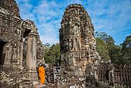 A monk visiting Bayon, inside Angkor Thom, at Angkor Archaeological Park in Siem Reap, Cambodia.