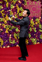 Ken Jeong takes a selfie with photographers whilst attending the Crazy Rich Asians Premiere held at Ham Yard Hotel, London.