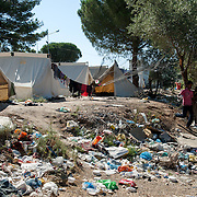 A man running through mountains of rubbish lying next to refugees tents in Moria camp.