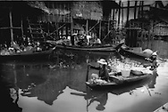 Fish mongers floating along the water main street of  Kompong Phhluk where goods are paddled to people's doorsteps, while men work on a boat engine in another boat Tonle Sap, Cambodia.