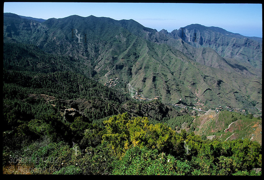 Panoramic overlook contrasts wet, forested slopes against arid, scrub-filled slopes of La Gomera island in the Canary Islands; Spain