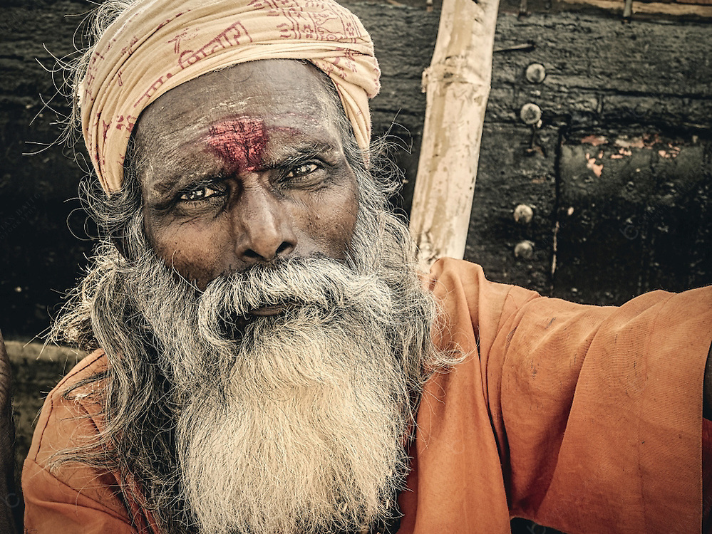 Beggar in sadhu clothes in Varanasi India. Sadhus are ascetics dedicated to achieving Moksha, liberation of the reincarnation cycle, through meditation and contemplation of Brahman. Many people in the city dress like sadhus only to receive money from the pilgrims and tourists that visit the city.