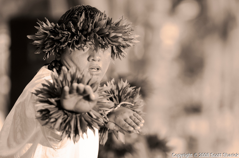 A young man in a classic hula pose in this sepia toned picture from Hawaii.