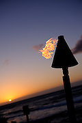 Burning oil lamp on beach at sunset, in silhouette. Kona, Big Island, Hawaii RIGHTS MANAGED LICENSE AVAILABLE FROM www.PhotoLibrary.com