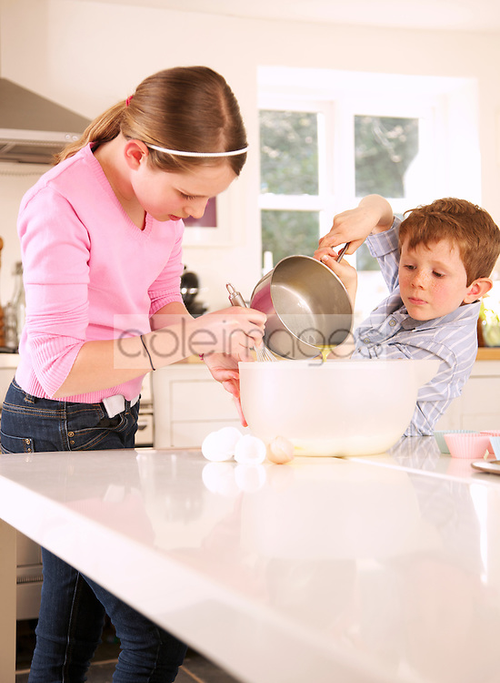 Girl and young boy preparing cupcakes