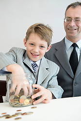 Father and son with piggy bank, smiling