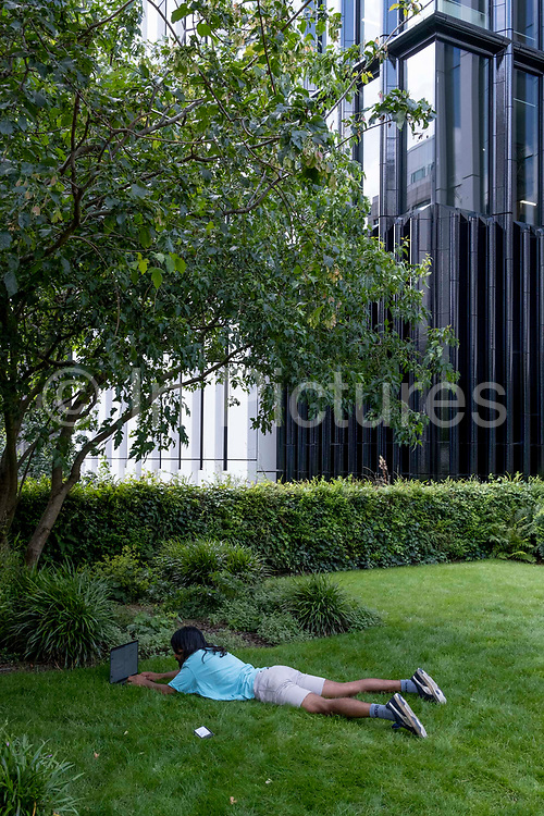 A day after the Covid Freedom Day, when social distancing and the wearing of face coverings are no longer mandatory, a man lies on the grass beneath largely empty office premises as the majority of City workers remain working from home, on 21st July 2021, in London, England.