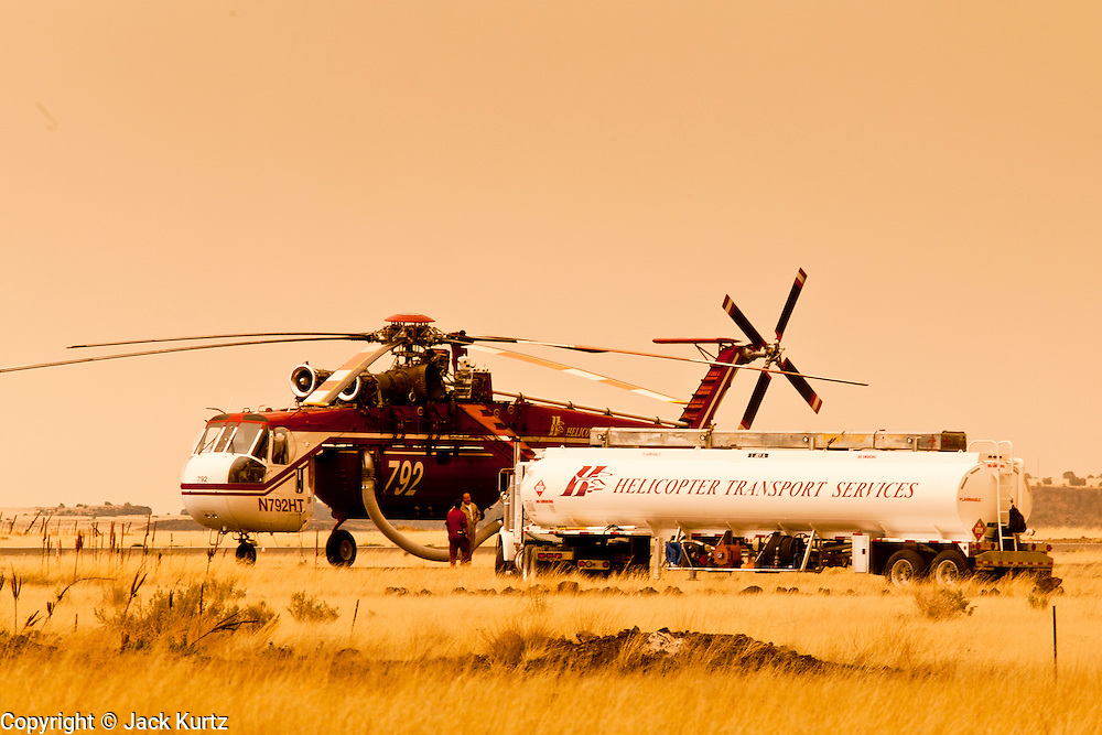 """04 JUNE 2011 - SPRINGERVILLE, AZ: Helicopters fighting the Wallow fire are refueling at the Springerville Airport. Smoke from the fire, more than 20 miles from Eagar, turned the sky bright orange. The fire grew to more than 140,000 acres early Saturday with zero containment. A """"Type I"""" incident command team has taken command of the fire.  PHOTO BY JACK KURTZ"""