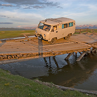 A four-wheel drive van crosses a dangerous, often-washed-out bridge over a river near Rinchenlhumbe in northern Mongolia's Darhad Valley.   Behind are the Horidal Saridag Mountains.