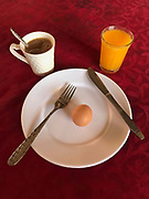 A breakfast of coffee, orange juice and a hard boiled egg on a white plate and a red tablecloth