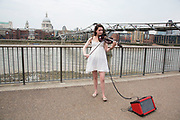 Young busker performing her violin music at Bankside. Bankside is a significant arts and entertainment district, and home to an endless list of activities for Londoners, visitors and tourists alike.