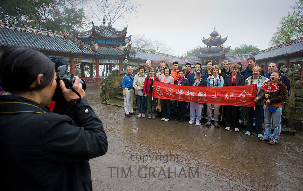 Visitors pose for a photograph with tour guide at the City of Ghosts in Fengdu, China