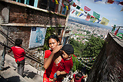A visitor to the Swayambhunath temple complex is making her way up the steep steps. The temle is also called the Monkey Temple and it is situated on top of a hill in the Kathamndu Valley.