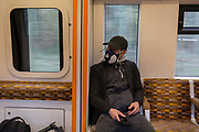 "As the UK government announces further Coronavirus-related restrictions to its citizens, with the immediate closure of pubs, cafes, gyms and cinemas, and the worldwide number of deaths reaching 10,000 with 240,000 cases, 953 of those in London alone, a male rail passenger wears an industrial maintenance free face mask made by 3M, a variety that gives ""Effective and comfortable protection against organic vapour and hazardous particulates"", on an Overground train travelling across south London, on 20th March 2020, in London, England."