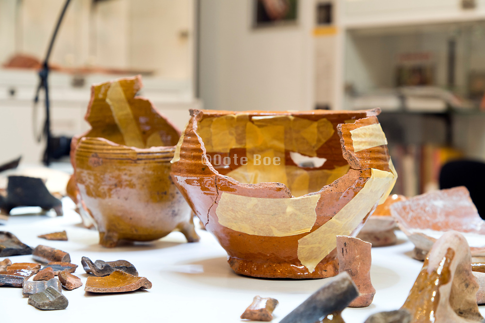 taping together of the broken pieces of an ancient pot in the Allard Pierson Museum Amsterdam
