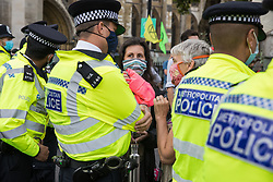 Metropolitan Police officers speak to climate activists from Extinction Rebellion who had occupied the road around Parliament Square during a Back The Bill rally on 1st September 2020 in London, United Kingdom. Extinction Rebellion activists are attending a series of September Rebellion protests around the UK to call on politicians to back the Climate and Ecological Emergency Bill (CEE Bill) which requires, among other measures, a serious plan to deal with the UK's share of emissions and to halt critical rises in global temperatures and for ordinary people to be involved in future environmental planning by means of a Citizens' Assembly.