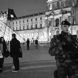 vendredi 25 novembre 2016, 21h09, Paris Ier. Militaire du 3ème Régiment d'Artillerie de Marine en patrouille de nuit dans la cour Napoléon parmi les touristes et promeneurs.