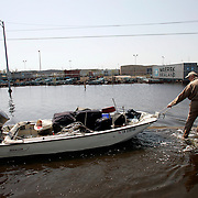 NEW ORLEANS, LA - September 4, 2005:  A man pulls his belongings in a boat after evacuating his flooded home on Sept, 4, 2005 in New Orleans following the destruction caused by Hurricane Katrina. (Photo by Todd Bigelow/Aurora)