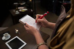 Cropped image of woman taking order while espresso and tablet kept on dining table at restaurant