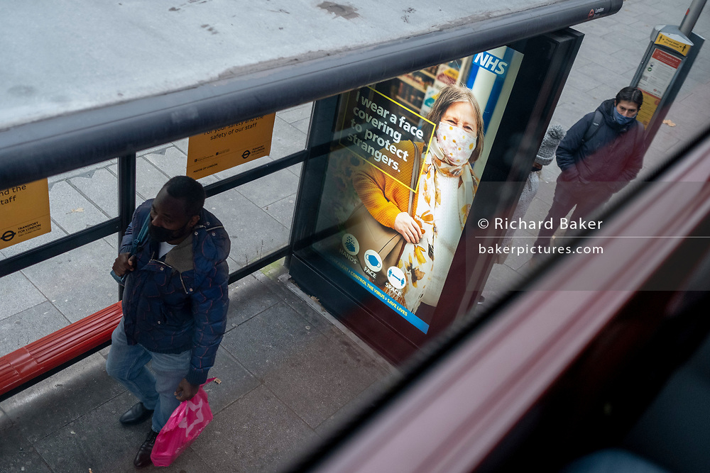 In advance of a re-opening of businesses and before a change to a Tier 2 for London during the second wave of the Coronavirus pandemic, an NHS (National Health Service) and urges travellers to wear a face covering at a bus stop in south London, on 30th November 2020, in London, England.
