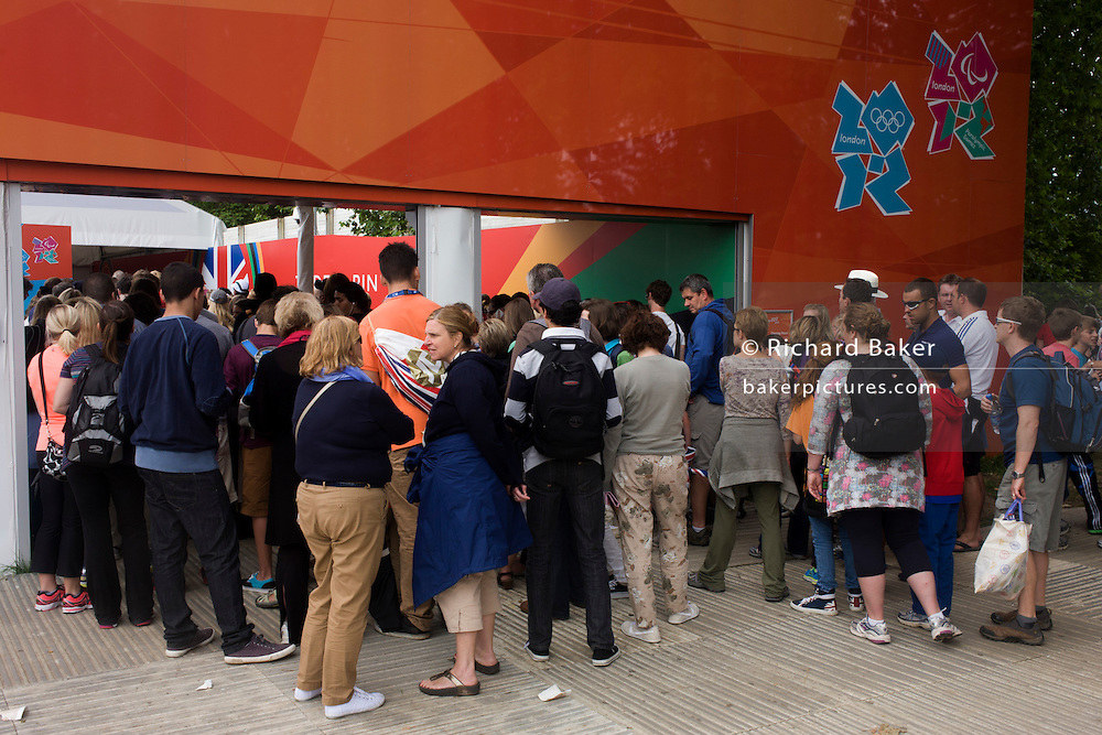 Queues and crowds at the entrance of the official London 2012 merchandise shop - hours before another successful gold medal win, this time by Team GB triathlete Alistair Brownlee in the men's Triathlon during the London 2012 Olympic Games. The mid-week event surprisingly drew huge crowds into the capital's largest public (royal) park for an event, not usually attracting families with children who all enjoyed the fine weather and easy temperatures. A London 2012 merchandise shop was set up on the southern side and parents and kids used the exterior hoarding featuring iconic London landmarks such as Nelson's Column, St Paul's Cathedral and Tower Bridge, to relax against after an early start from homes around the country