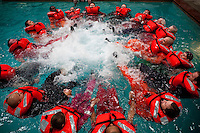 Participants form a survival circle to improve visibility in open water by aircraft during a class in open water survival techniques, taught by Garrett Hindt in Brookshire, TX. All workers, contractors and visitors are now required to do the training, which also incorporates a simulated helicopter crash (in a swimming pool) and emergency steps used to free oneself while underwater.
